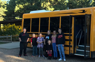 Chevelon Butte students standing in front of school bus