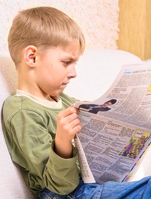 Boy reading a newspaper