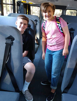 Two Chevelon Butte students posing together on a bus