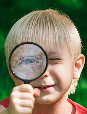Boy holding a magnifying glass up to his eye