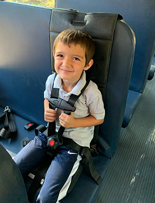 Young student buckled up on a bus seat