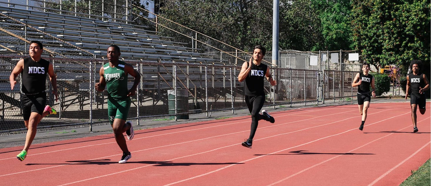 track team members running on track