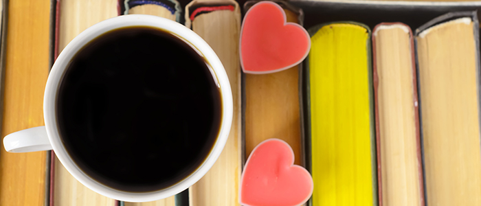 A cup of black coffee and two heart cookies