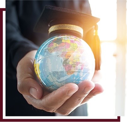 Adult hand holding a globe of the earth with a graduation cap on top