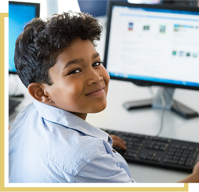 little boy smiling while working at his computer