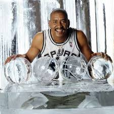 George Gervin posing with basketball trophies