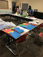 Folder supplies on table with volunteers working