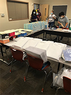School materials on table with volunteers working