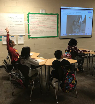 Student raising their hand in a classroom