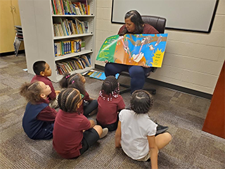 Teacher reading to students sitting on the floor