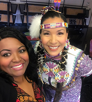 Two staff members posing together as one is dressed in Native American attire