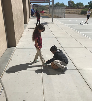 Female student helping another student tie their shoe