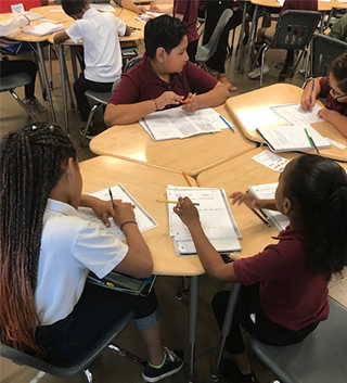 Students working on classwork at a table together