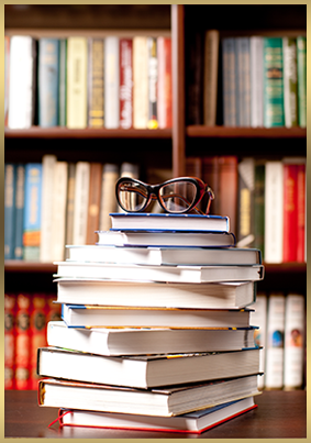 Glasses sit on top of stacked books in front of bookshelves