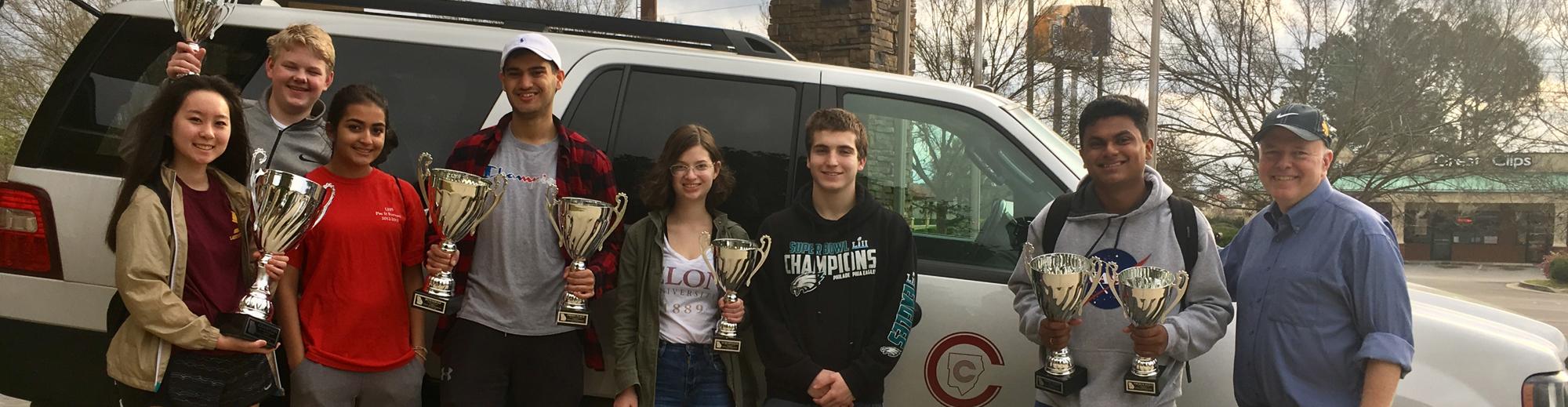 Debate team members holding trophies