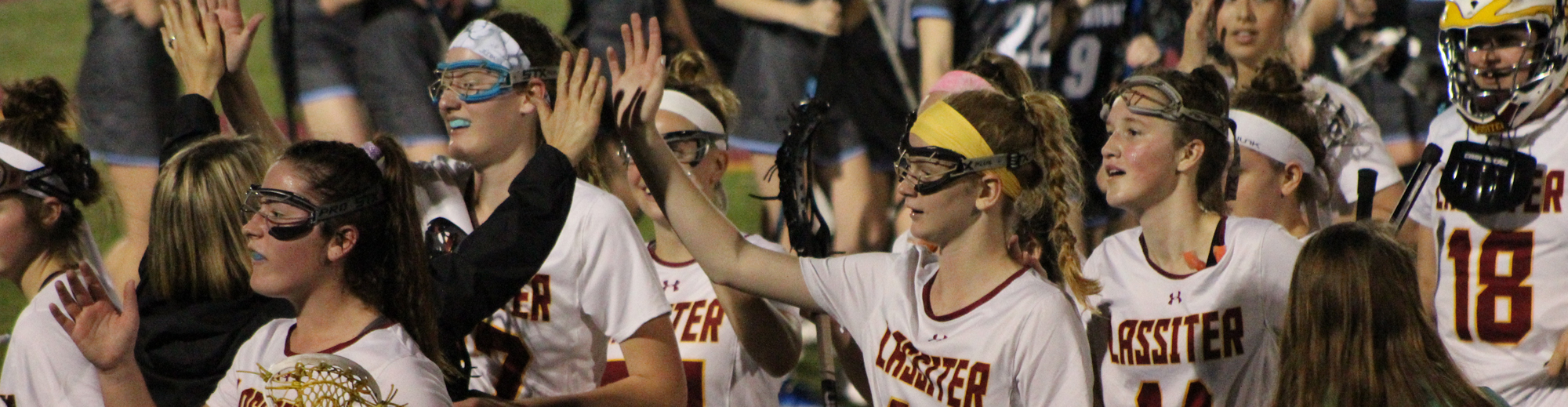 Girls Lacrosse team high fiving each other at a game