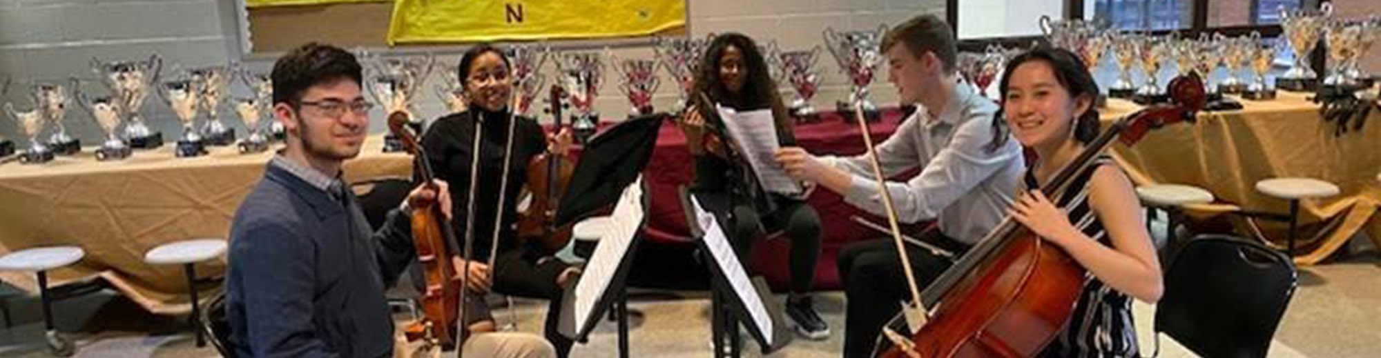 Group of students sitting with their stringed instruments
