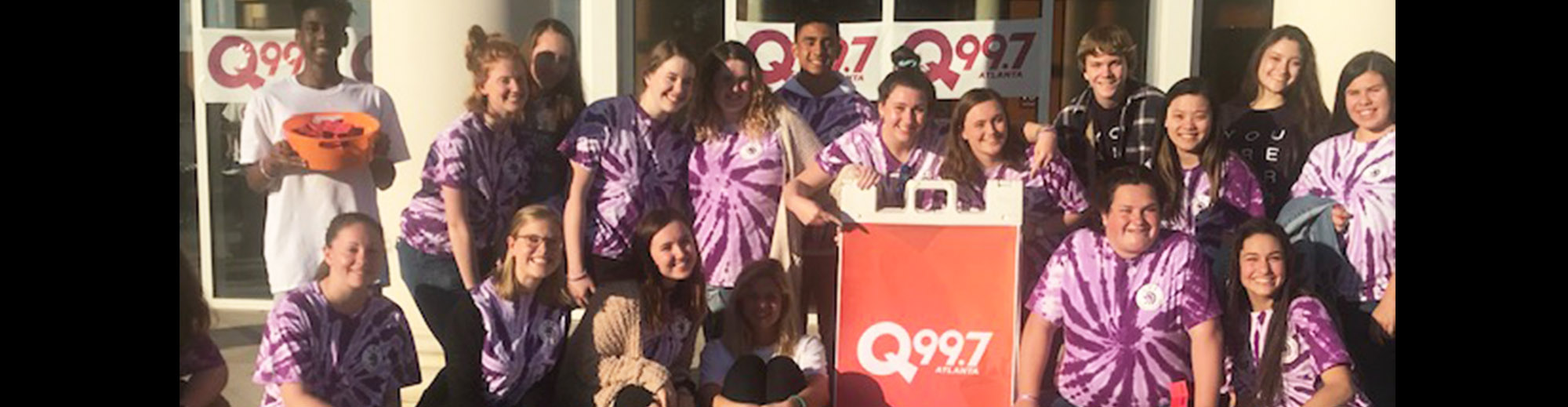Group of happy Lassiter students next to a Q99.7 sign