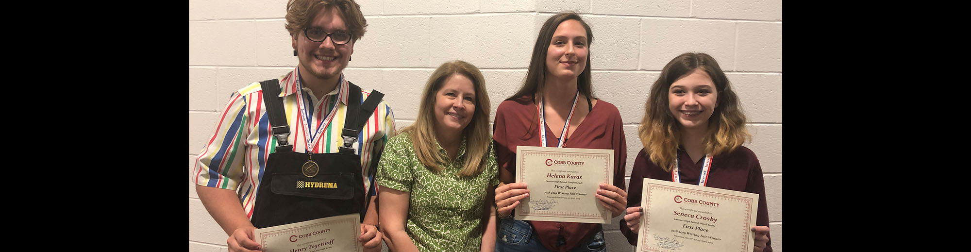 Three students with teacher posing with their 2018-2019 Writing Fair Winner certificates