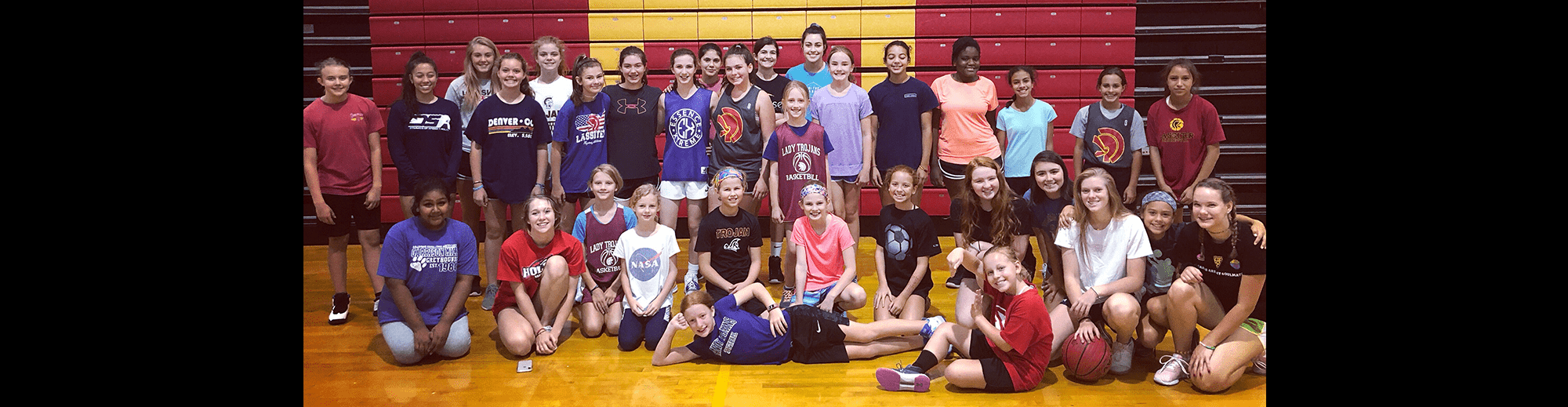 Basketball camp members pose together in a gym
