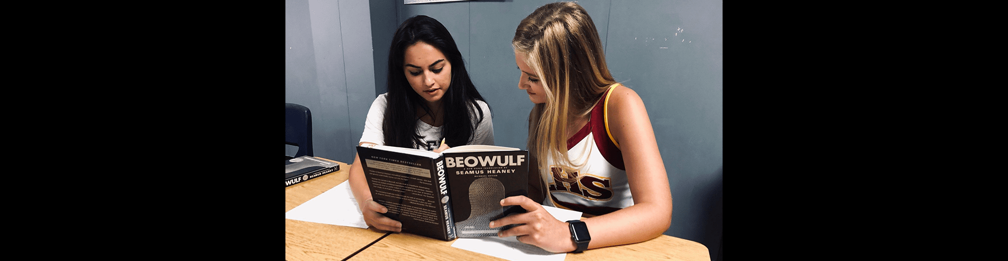 Two female students read a copy of Beowulf as they sit at their desks