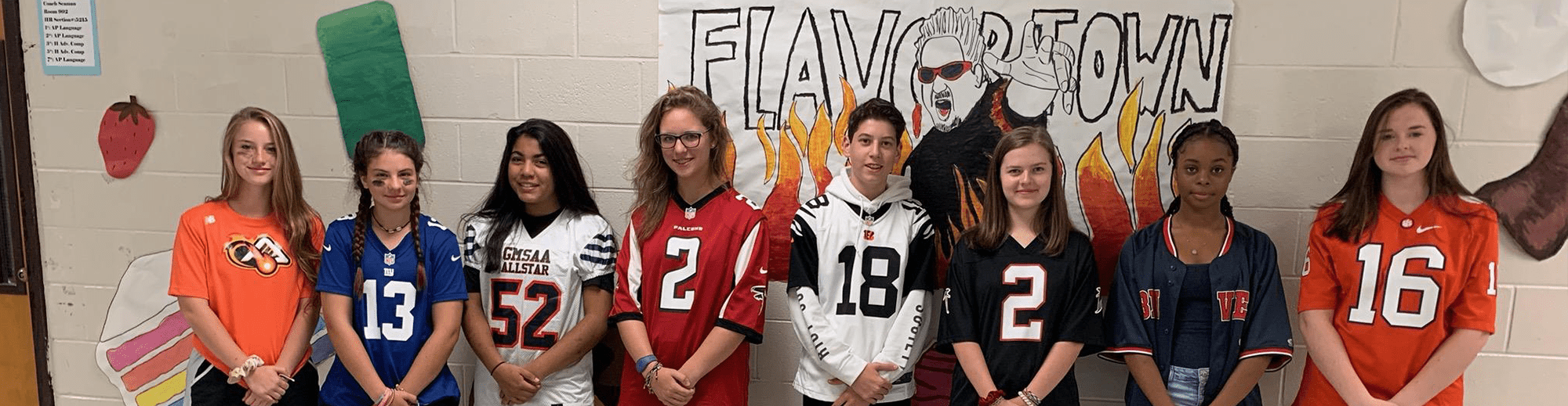 Students wearing athletics jerseys pose in front of a drawing of Guy Fieri and the word Flavortown