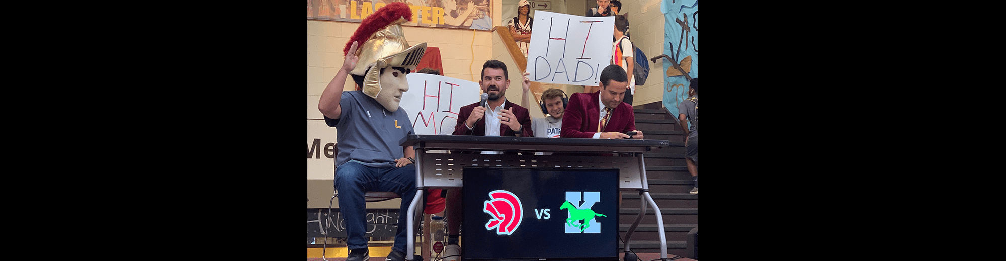 Trojan mascot sits next to a man with a microphone as students hold signs in the background