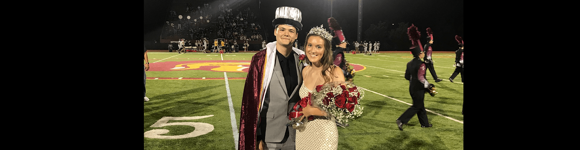 Homecoming king and queen pose together on the football field