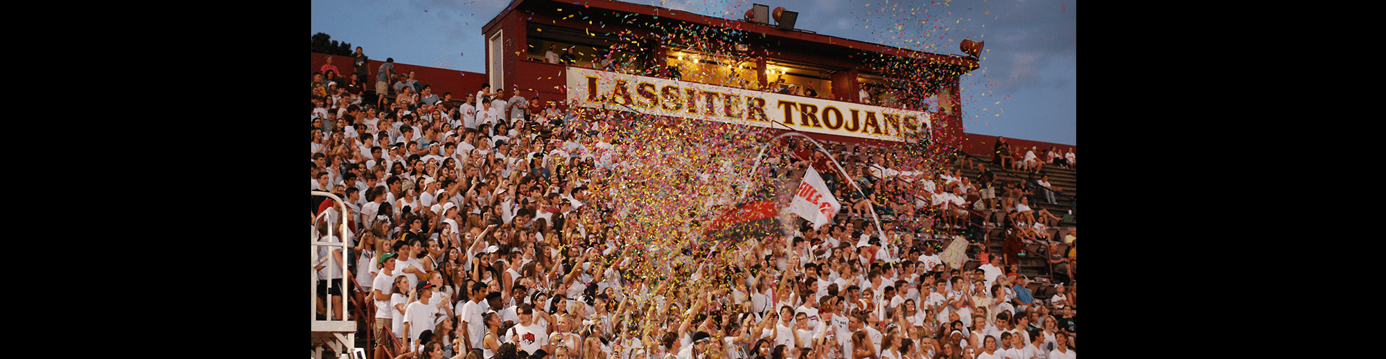 Students participate in an outdoor pep rally with confetti as they sit on bleachers in front of a Lassiter Trojans sign