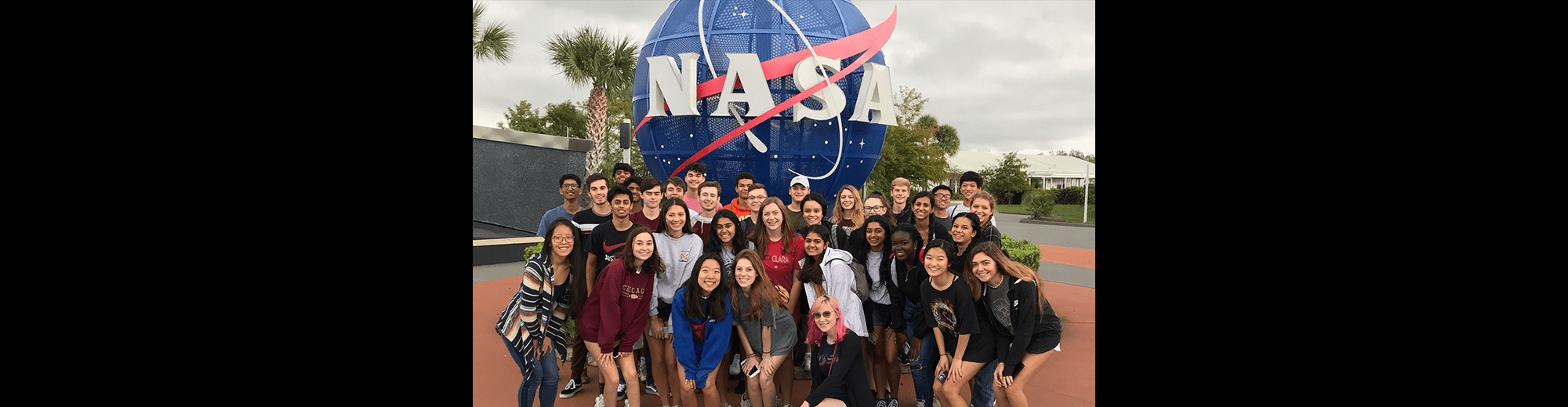 Students posing in front of a NASA sign