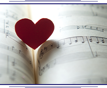 Paper heart cut out sits inside of a book of sheet music