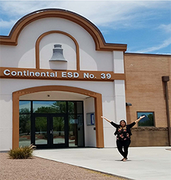 Mrs. Cuevas poses in front of Continental ESD No. 30 buidling