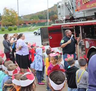 students and staff talking with firefighters and looking at a firetruck
