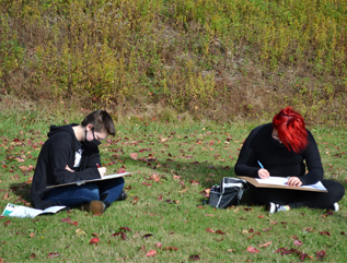 two students sitting in grass while working on an art project