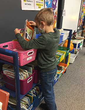 student getting books in a classroom