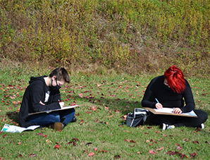 Two students reading outside