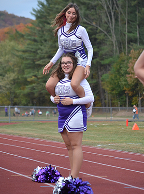 One Cheerleader on an other student's shoulders