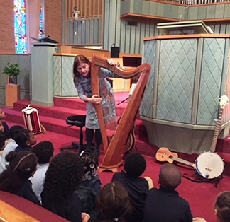 Teacher showing students how to play harp