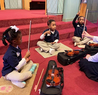 Students learning how to play violin