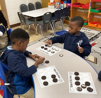 Two boys having fun with cookie learning activity