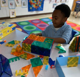 Boy in classroom building with shapes