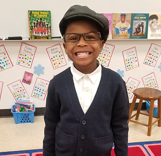 Smiling student dressed up with a sweater and cap