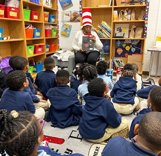 Adult wearing Dr. Seuss hat reading story to students