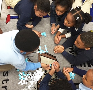 Group of students working together on the classroom floor