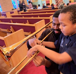 Elementary student learning how to play a horned instrument