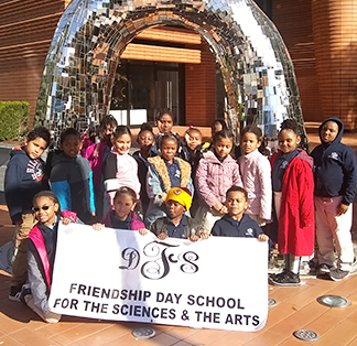 Group of students outside with an Friendship Day School banner