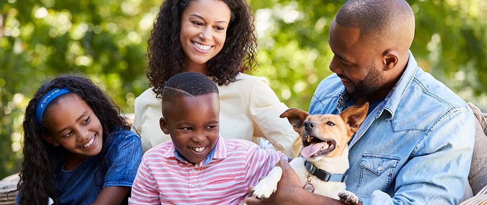 Family smiling while playing with dog