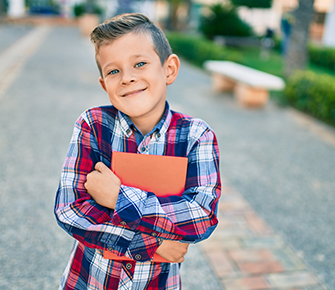 Adorable student boy outside with notebook