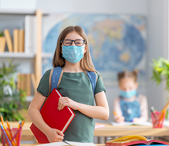 Happy student returns to school wearing a face mask