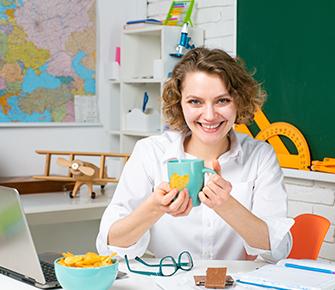 Happy teacher sitting at her desk